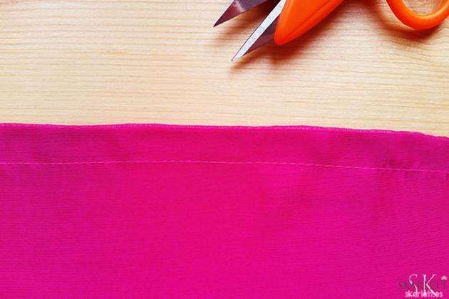 detalle de costura francesa en tela de gasa color rosa sobre una mesa de madera y con cortahilos naranja