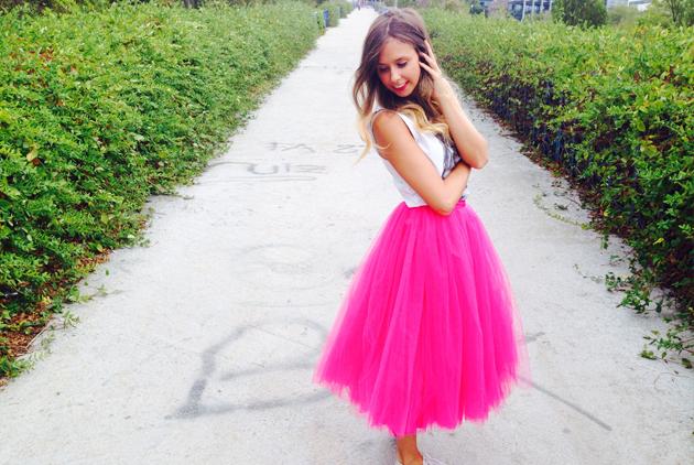chica en jardin con setos a los lados y suelo gris y con falda de tul en color rosa intenso