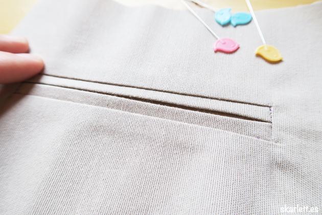 detalle de bolsillo ribeteado acabado con alfileres de colores con forma de pajaro