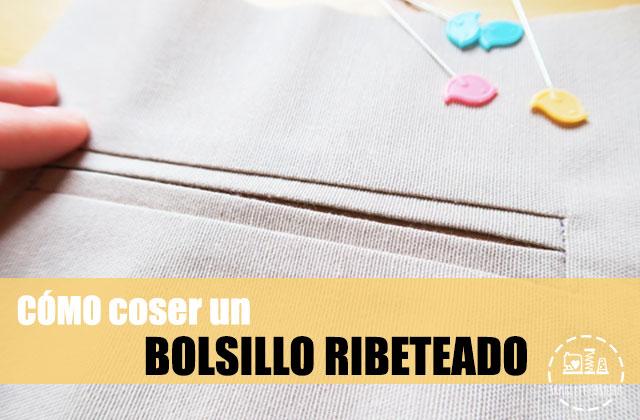 bolsillo ribeteado en tela color arena con alfileres de colores