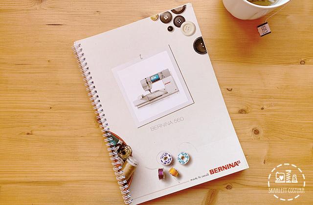manual de instrucciones de la maquina de coser bernina 560 sobre mesa de madera al lado taza blanca de ceraminca con un te verde de la marca JOE´S TEA Co